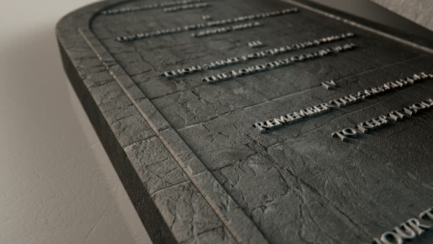 A slow close up zoom out of two stone tablets with the ten commandments inscribed onto them on an isolated background