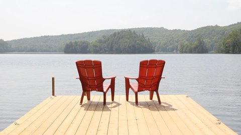 Two red chairs on cottage dock. Sunny morning. Medium shot. Two red chairs on a floating wooden dock. Sunny morning in Haliburton county, Ontario, Canada. Medium shot.