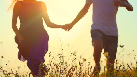 Happy couple having fun outdoors. Couple running away on the meadow. Countryside. Young Man and woman holding hands and running through a field with wild flowers. Sun flare. Slow motion video footage