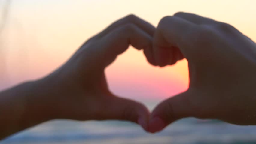 Beauty girl making heart with her hands over sea background. Happy young woman. Silhouette hand in heart shape with sunset inside. Vacation concept. Summer holidays. Tourism. Slow motion 240 fps 1080p #7091377