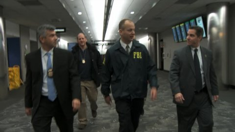 CIRCA 2010s - FBI agents and Homeland Security walk through an airport.