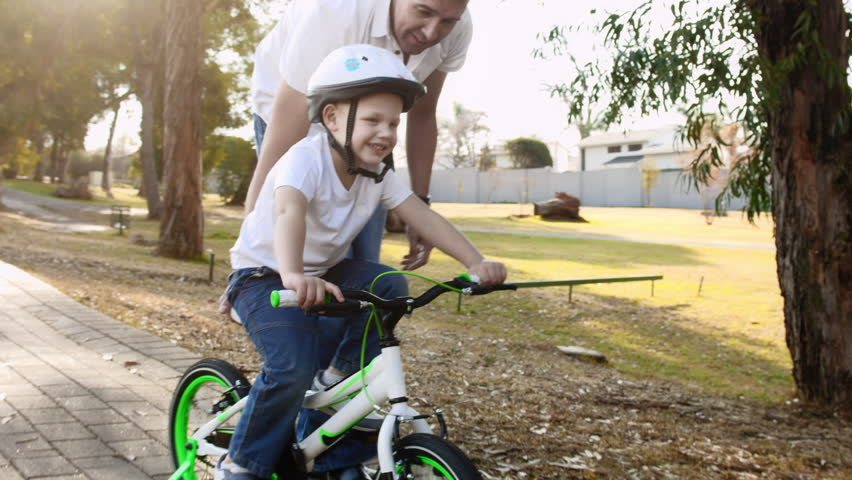 Steadicam shot of father teaching son how to ride his bike on a park pathway with safety helmet. #7140847