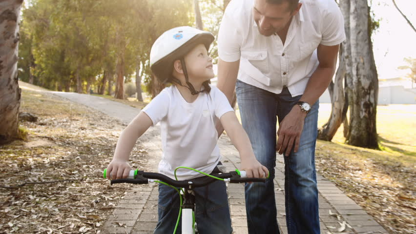 Steadicam shot of father teaching son how to ride his bike on a park pathway with safety helmet. | Shutterstock Video #7140856