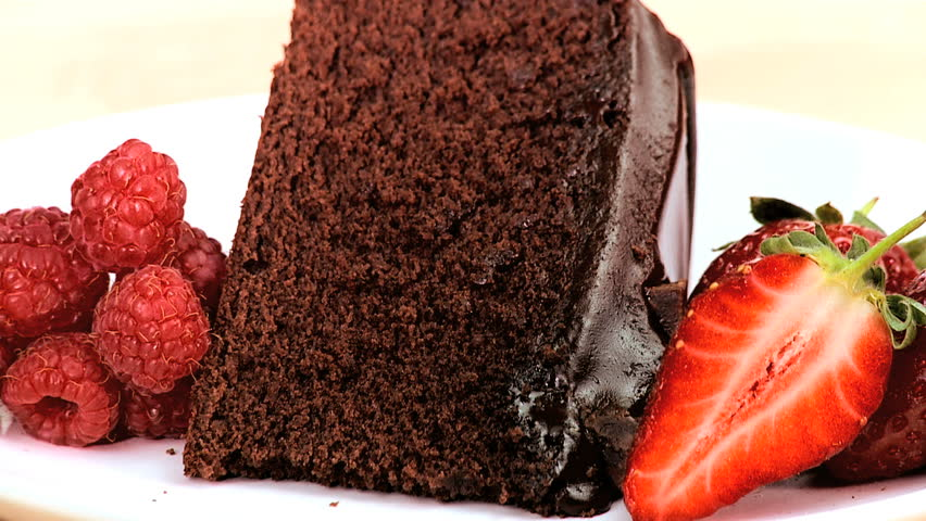 Indulgent chocolate cake & strawberries being covered in sweet sticky sauce on white background