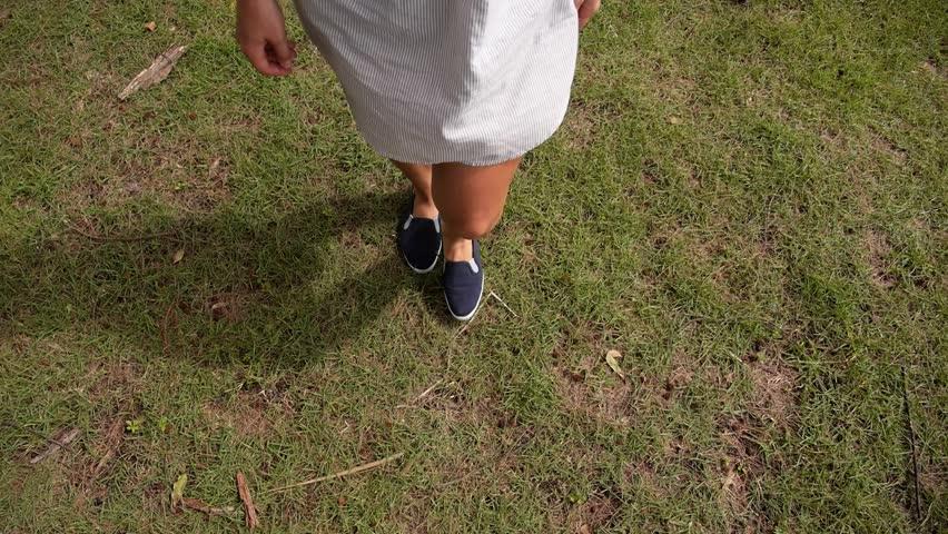 Young Female Legs in Sneakers Walking on the Grass. Slow Motion. HD, 1920x1080. | Shutterstock HD Video #7250449