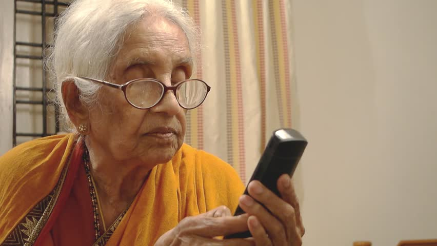 A very old 90 year India / Asian woman using the phone and calling