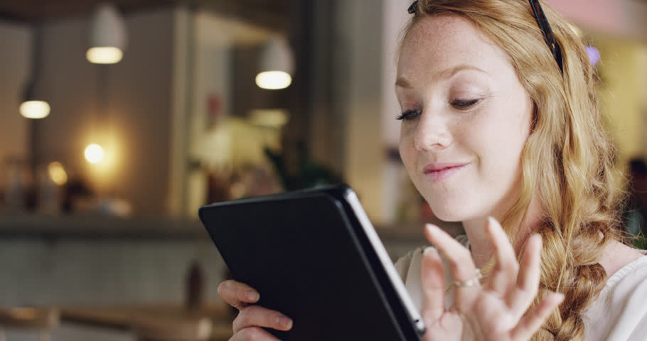 Beautiful young woman using ipad tablet touch screen in cafe