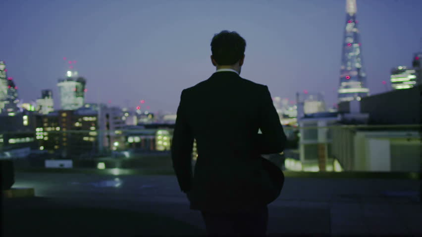 Successful businessman looks out at the view of the London city skyline at night #7371007