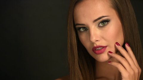 Closeup face of a beautiful young woman shows the red nails. Fashion model with brown eye makeup.