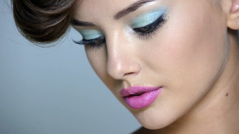 Closeup face of a beautiful  girl with blue eye makeup and pink lips. Full hd video footage  clip 1080.