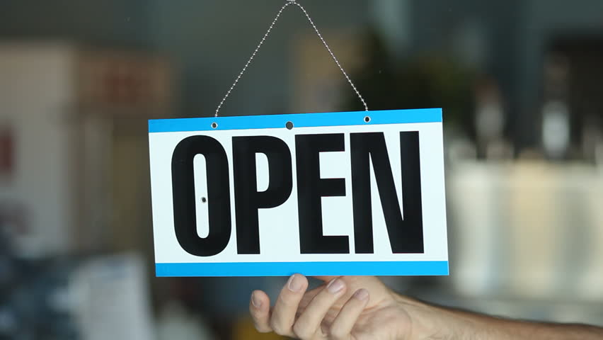 Business owner turning an open for business sign in their storefront window. | Shutterstock HD Video #7410202