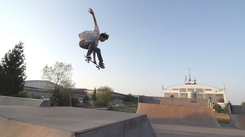 Slow Motion Shot Of A Skilled Skateboarder Mastering Performing An Ollie In Skateboard Park
