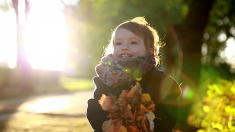 Kid throws yellow leaves in autumn park.