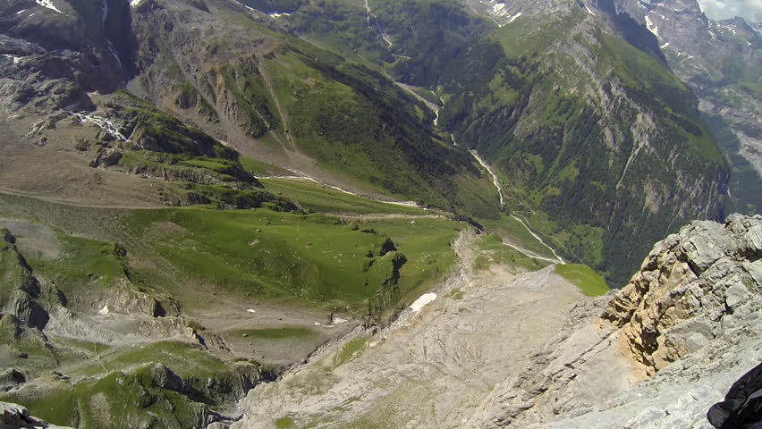A base jumper in a wingsuit leaps off from a cliff, gliding down over a green landscape, POV