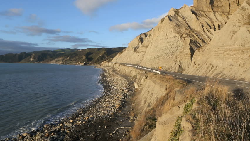 Coastal road next to cliffs prone to erosion at Palliser Bay, New Zealand