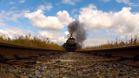 Steam Locomotive coming down railroad tracks right at camera shot on ground level.