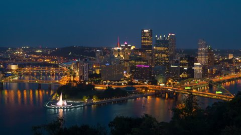 (Time-lapse/Zoom-in) Night falls on the downtown area of Pittsburgh, Pennsylvania including the skyline, bridges, and Point State Park at the confluence of the Allegheny and Monongahela Rivers.