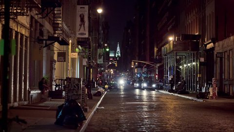 NEW YORK - AUG 1, 2014: people crossing dark SoHo cobblestone street at night with Chrysler Building and car headlights in background. SoHo is a neighborhood south of Houston Street in Manhattan, NYC.