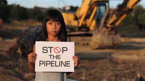 A young First Nations girl proactively demonstrates against the proposed oil pipeline running through her province in Canada.