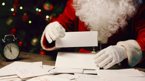 Tilt up from heap of letters to Santa Claus face