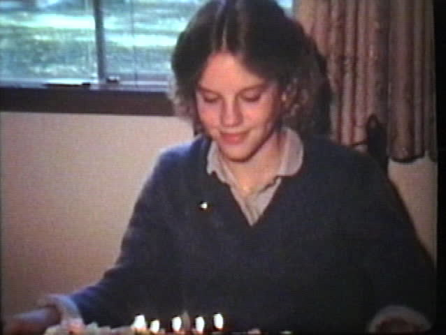 A cute teenage girl blows out the candles on her birthday cake several times.