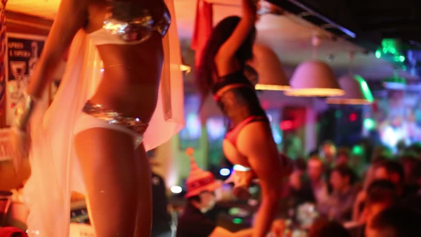 Women in angel and daemon costumes dance on bar in night club
