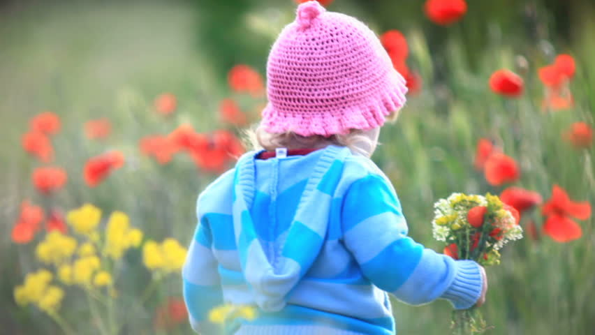 Child spinning with flowers in their hands. He looks into the camera