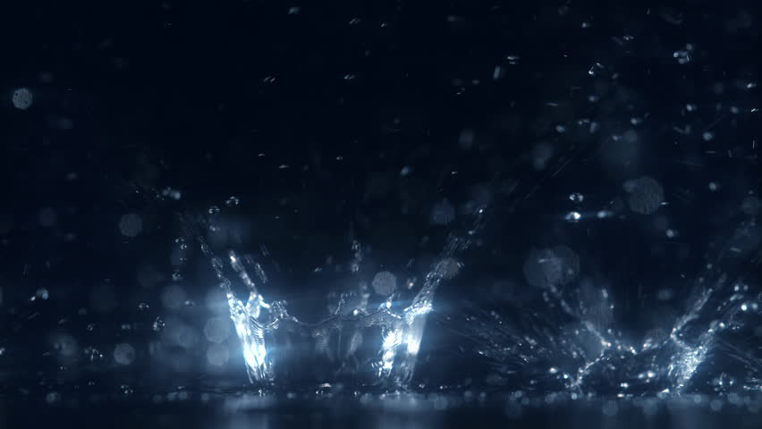 Water Drop making ripple against black background. Shot with high speed camera, phantom flex 4K. 4K 30fps. Slow Motion.