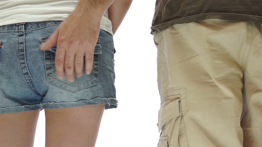 Isolated on white shot of a man slaps the backside of a woman standing next to him in a sexual and flirtatious manner.