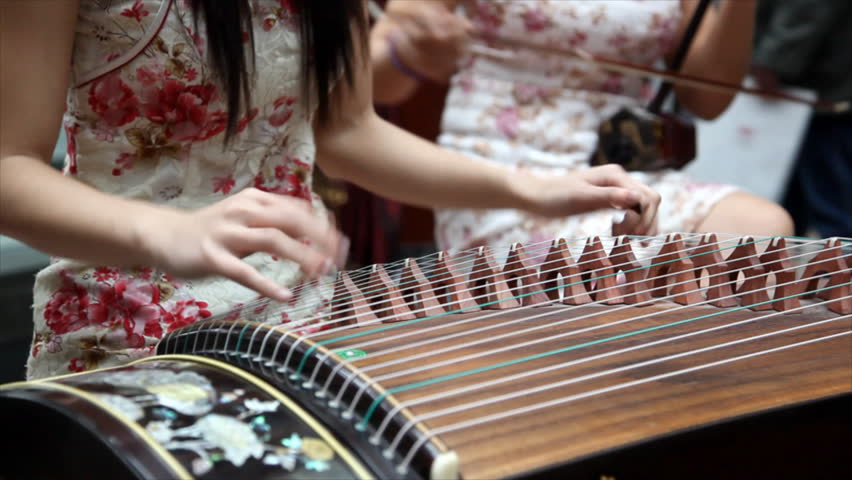 Chinese traditional musician playing chinese guzheng.Guzheng, also called zheng or Chinese plucked zither,is a plucked half-tube zither with movable bridges and  strings.