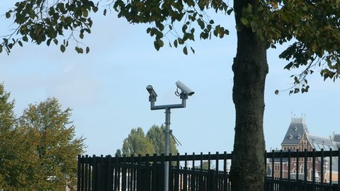 Two security cameras look out over a steel fence, shaded by a tree. A bus rides through the shot, partly obscuring the view, after which they return in sight.