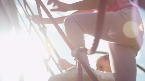 Two young girls climbing on a rope climbing frame on a sunny day in slow motion, shot on RED EPIC