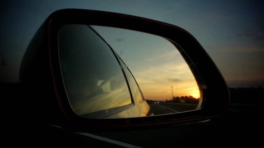 Car driving with vivid sunset (sun going down) in read side mirror. Other cars are reflected as well as the trees and bridges   | Shutterstock HD Video #7800856