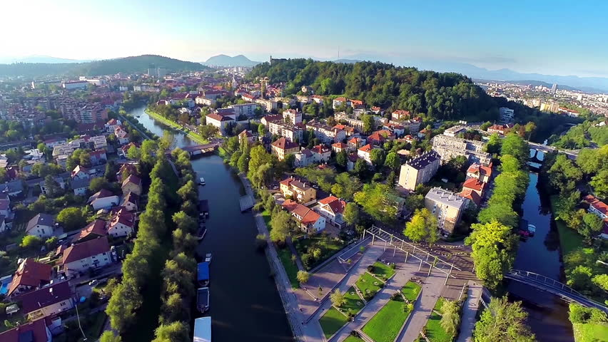 Aerial shot of Ljubljana city with Ljubljanica and castle at sunset. Flying above beautiful city with landscape view of river, castle and green hills.