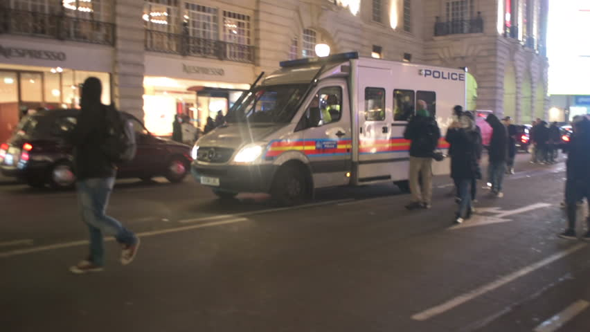 LONDON, UK - NOV 5: Three British Police vehicles arrive on the scene of a demonstration with sirens and lights and are surrounded by protesters in London on November 5, 2014