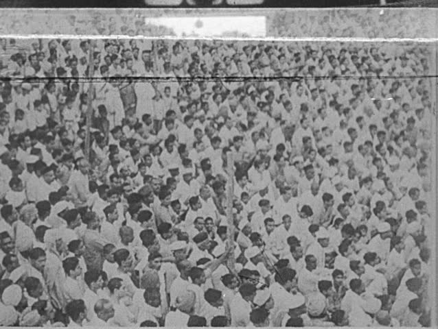 INDIA- CIRCA 1930: A large crowd of Indians, all dressed in white. Gandhi sits on a pedestal. Gandhi stands among a crowd.  Small crowd of pedestrians walk about an outdoor market on an urban street.