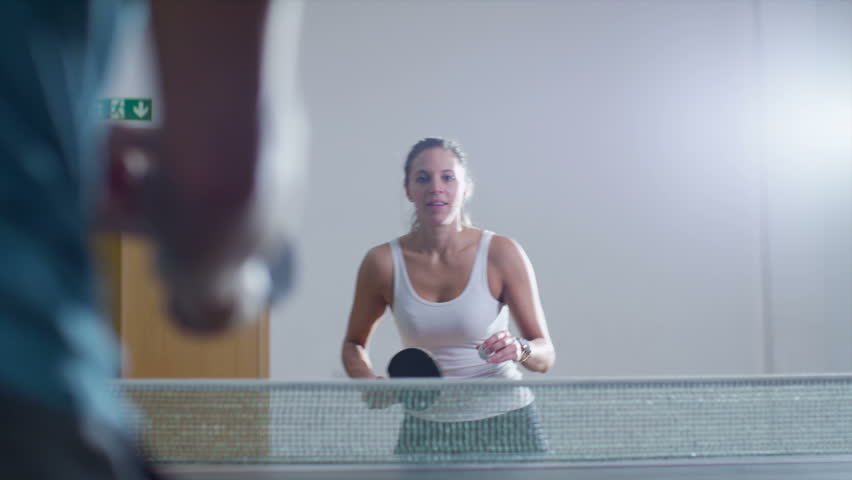 Slow motion shot of an attractive young woman playing table tennis