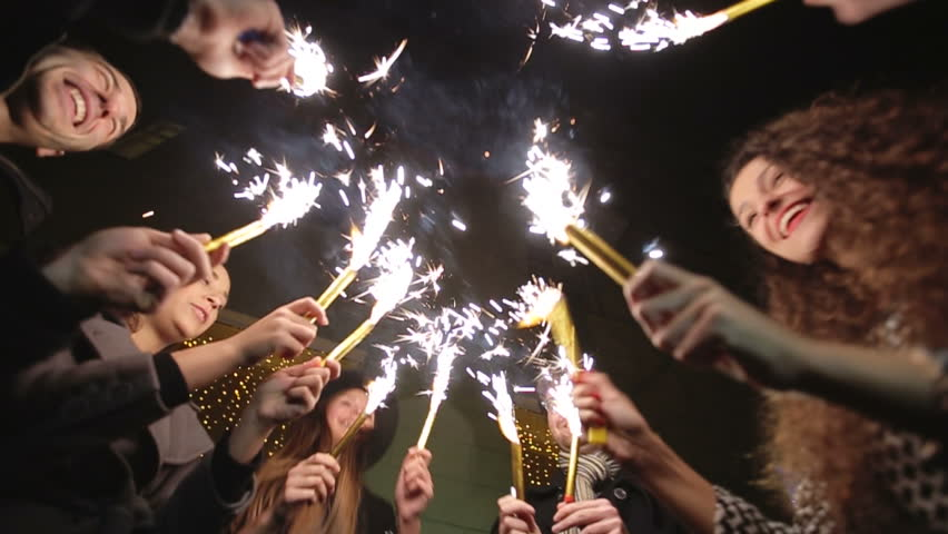 Group of people dancing with sparklers. Slow motion