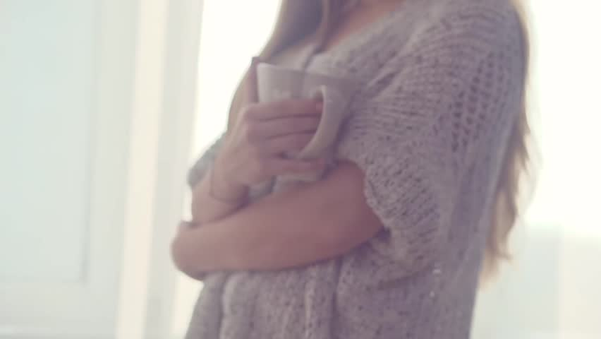 Beauty girl looking out the window and enjoying her morning coffee or tea. Beautiful young romantic woman drinking hot beverage at home. Slow motion footage 240 fps. HD 1080. High speed camera shot