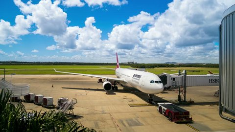 BRISBANE - 12 JAN: Timelapse view of a Qantas Jet at the Brisbane airport being loaded with luggage as other planes take off in the background on 12 January 2014 in Brisbane, Australia