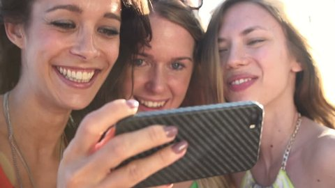 Three female friends taking selfie on mobile phone shot against the sun in slow motion. Shot on Sony FS700 at a frame rate of 100fps