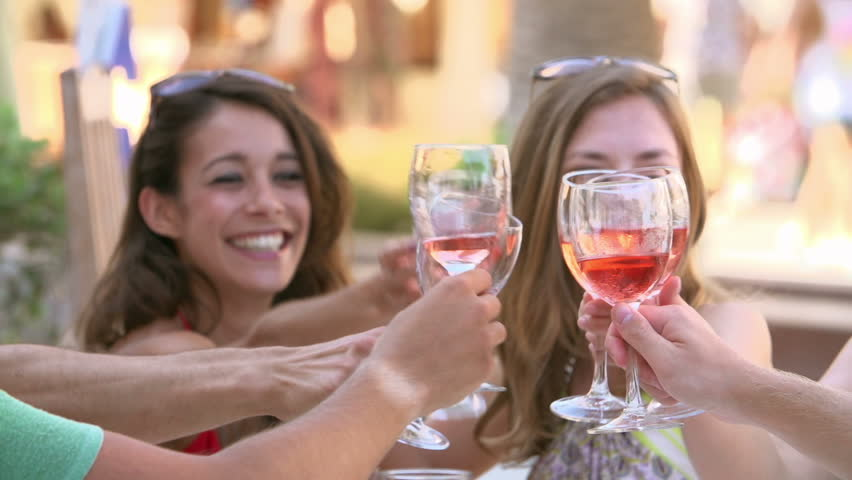Group of young friends enjoy a glass of wine at outdoor bar - they make a toast in slow motion.Shot on Sony FS700 at a frame rate of 50fps #7924657