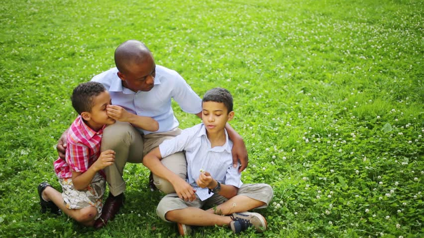 Father sitting on his haunches and hugs his sons on a glade in the park