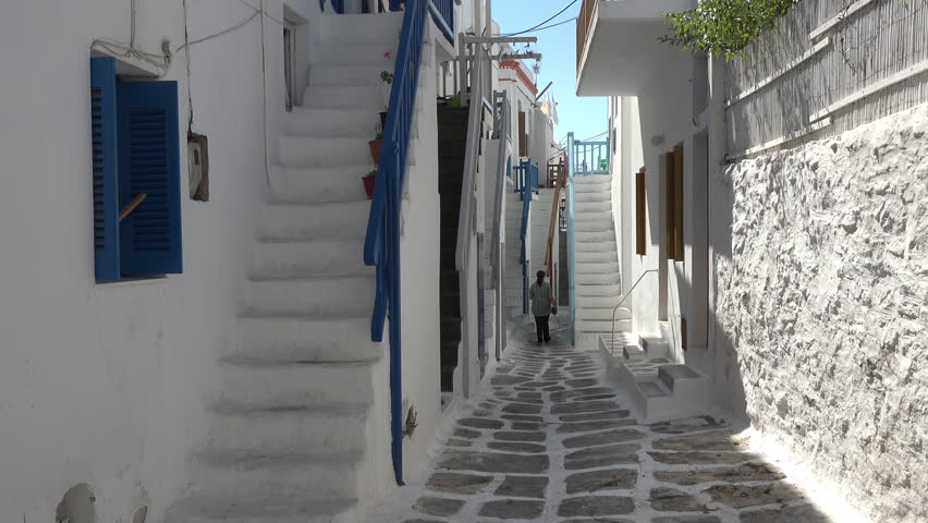 MYKONOS, GREECE   SEPT 2014: Mykonos Greece Woman White Washed Street  Alley. Destination