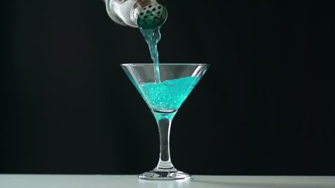 Close up of unrecognizable cropped bartender pouring blue cocktail from shaker to cocktail glass