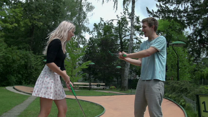 Man and women sword fighting with golf clubs slow motion. Wide shot of romantic couple playing mini golf and enjoy sword fighting.