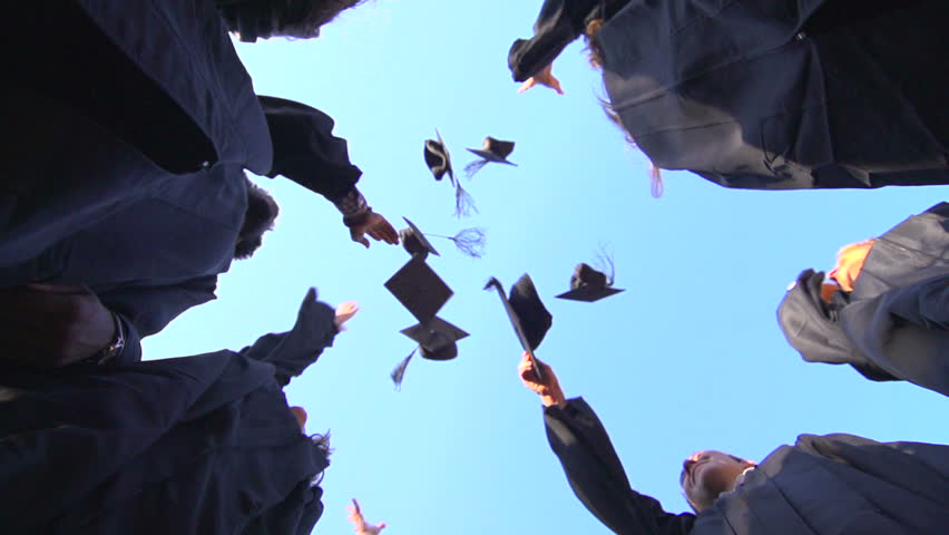 A slow-motion shot from below of a group of racially-diverse students throwing their graduation mortarboards in the air in celebration. #7971607