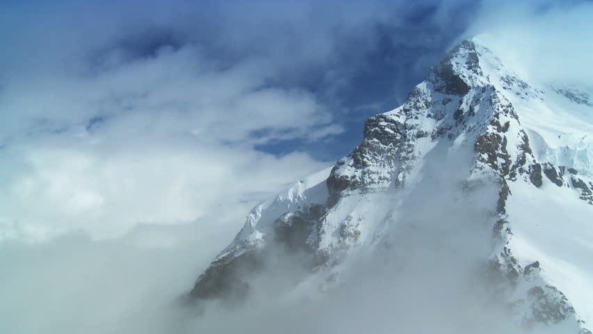 Time-lapse clouds over dramatic snow covered Monch mountain in Swiss Alps