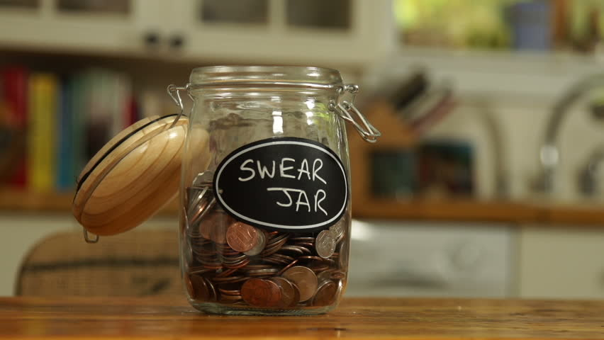 An anonymous person drops some loose change into a saving jar, which has Swear Jar written on it