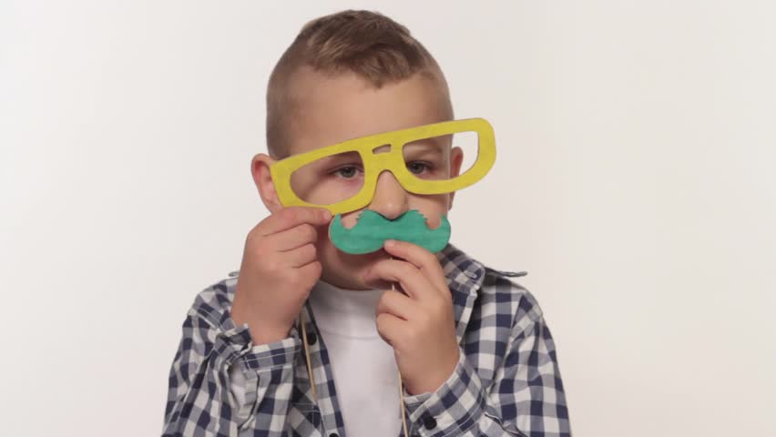 Boy playing with toy mustaches | Shutterstock HD Video #7977406